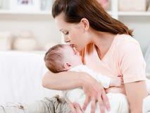 Moeder die haar slaapbaby kust Royalty-vrije Stock Fotografie