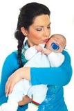 Moeder die haar slaapbaby kust Stock Afbeeldingen