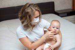 Moeder die haar zieke baby houden die een masker dragen royalty-vrije stock afbeelding