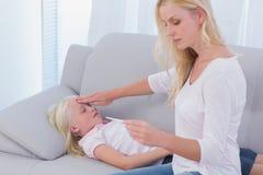 Moeder die haar zieke dochter behandelen royalty-vrije stock afbeelding