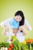 Moeder die haar zoon helpen salade maken Royalty-vrije Stock Afbeelding