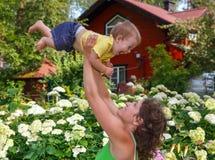 Moeder die haar zoonshoogte in openlucht opheffen Royalty-vrije Stock Afbeeldingen