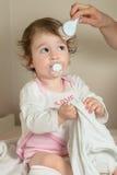 Moeder die het haar van haar leuk babymeisje met haarborstel na douche kammen Royalty-vrije Stock Afbeeldingen