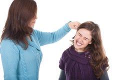 Moeder die het oor van haar dochter trekt royalty-vrije stock afbeeldingen