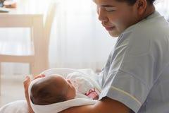 Moeder die het pasgeboren meisje van de zuigelingsbaby in wapen houden Royalty-vrije Stock Afbeeldingen