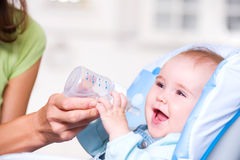 Moeder die het water geeft aan baby Stock Afbeelding