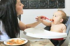 Moeder die hongerig halfjaarlijks oud babyvast lichaam voeden Royalty-vrije Stock Foto