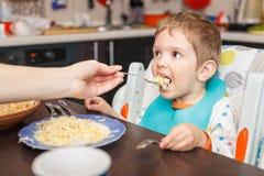 Moeder die hongerige jongen in highchair binnen voeden royalty-vrije stock foto