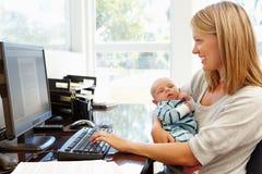 Moeder die in huisbureau werken met baby Royalty-vrije Stock Fotografie