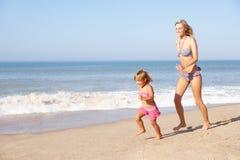 Moeder die jong meisje op strand achtervolgt Royalty-vrije Stock Afbeeldingen