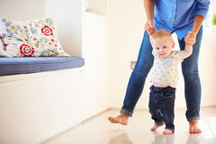 Moeder die Jonge Zoon helpen aangezien hij leert te lopen Stock Afbeelding