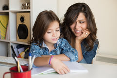 Moeder die kind met thuiswerk helpen Stock Fotografie