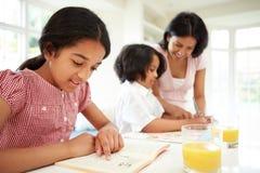 Moeder die Kinderen met Thuiswerk helpen Royalty-vrije Stock Afbeeldingen