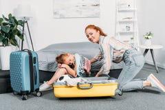 moeder die kleren in koffer proberen in te pakken terwijl aanbiddelijke dochterzitting stock foto