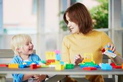 Moeder die kleurrijke bouwblokken met haar zoon spelen Royalty-vrije Stock Fotografie