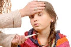 Moeder die koorts van haar ziek kind meten stock afbeeldingen