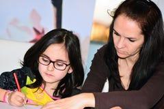 Moeder die meisje helpen om thuiswerk te doen Stock Afbeelding