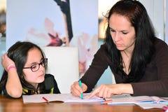 Moeder die meisje helpen om thuiswerk te doen Royalty-vrije Stock Afbeeldingen