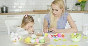 Moeder die meisjes kleurende eieren bekijken stock videobeelden