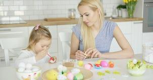 Moeder die meisjes kleurende eieren bekijken Royalty-vrije Stock Afbeeldingen