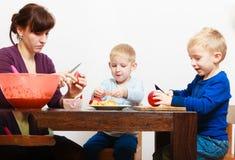 Moeder die met de kinderenjonge geitjes van zonenjongens vruchten appelen thuis snijden Stock Foto