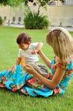 Moeder die met haar weinig zoon op gras speelt Royalty-vrije Stock Foto's