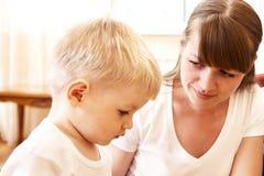 Moeder die met haar zoon spreekt stock afbeelding