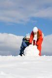 Moeder die met jong geitje sneeuwman maakt stock foto