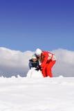 Moeder die met jong geitje sneeuwman maakt stock fotografie