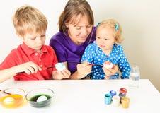 Moeder die met jonge geitjes eieren schilderen voor Pasen Stock Fotografie