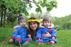 Moeder die met jonge tweelingen op een groene weide in vroege sprin zitten Royalty-vrije Stock Afbeeldingen
