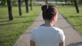 Moeder die met kinderwagen in groen park met baksteenweg lopen, slowmotion schot stock video