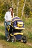 Moeder die met kinderwagen loopt Stock Afbeeldingen