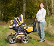 Moeder die met kinderwagen loopt Stock Foto