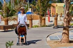 Moeder die met slaapbaby wandelen op strand stock foto's