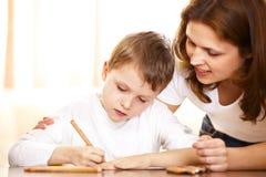 Moeder die met thuiswerk aan haar zoon helpt Stock Afbeelding