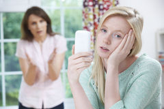 Moeder die met Tienerdochter over Gebruik van Mobiele Telefoon debatteren stock afbeelding