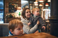 Moeder die met twee jonge geitjes in koffie op orde wachten stock fotografie