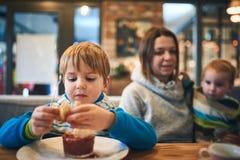 Moeder die met twee jonge geitjes in koffie op orde wachten stock foto's