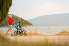 Moeder die met wandelwagen lopen, die van moederschap genieten bij zonsondergangland stock fotografie