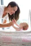 Moeder die met zuigelingskind glimlachen in bed Stock Fotografie