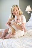 Moeder die mollige oude baby koestert van zeven maanden Stock Afbeelding