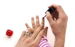 Moeder die nagellak toepassen op haar geïsoleerd meisje royalty-vrije stock afbeelding
