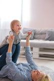 Moeder die op de vloer liggen die haar leuke baby houden Royalty-vrije Stock Fotografie