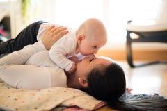 Moeder die op de vloer liggen die haar leuke babyzoon houden Stock Foto's