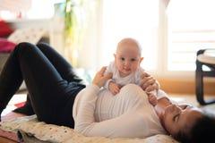 Moeder die op de vloer liggen die haar leuke babyzoon houden Royalty-vrije Stock Foto's