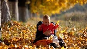 Moeder die op haar terug op de herfstgebladerte leggen en met baby, glimlachend kind spelen stock footage