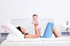 Moeder die op het bed ligt en met baby speelt Stock Foto