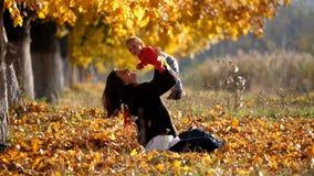 Moeder die op omhooggaande baby dicht bij de herfstboom opheffen, ouder kussend kind in het park stock video
