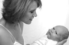Moeder die pasgeboren baby bewondert Stock Afbeelding